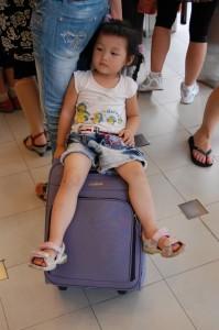 Besser als stehen: Glück für ein Kind dessen Eltern einen Trolley als Kinderwagen dabei hatten.